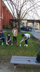 Students preparing to drop Mentos into various sodas, with gushing results.