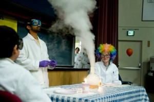 people watching a smoking chemical reaction