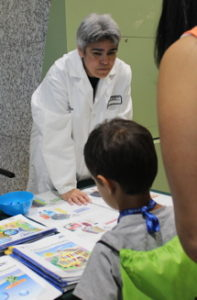 Chemist stands at table with child