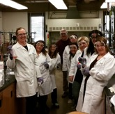 people in a chemistry lab holding various experiments