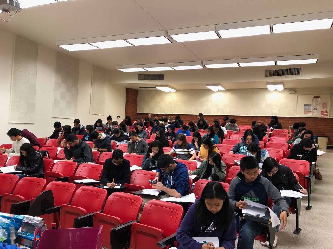Students taking exam in lecture hall