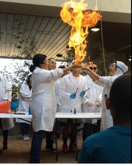students appearing to hold fire in their hands for a chemistry demonstration